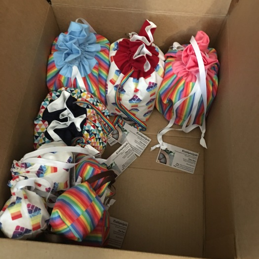 Box of rainbow drawstring bags