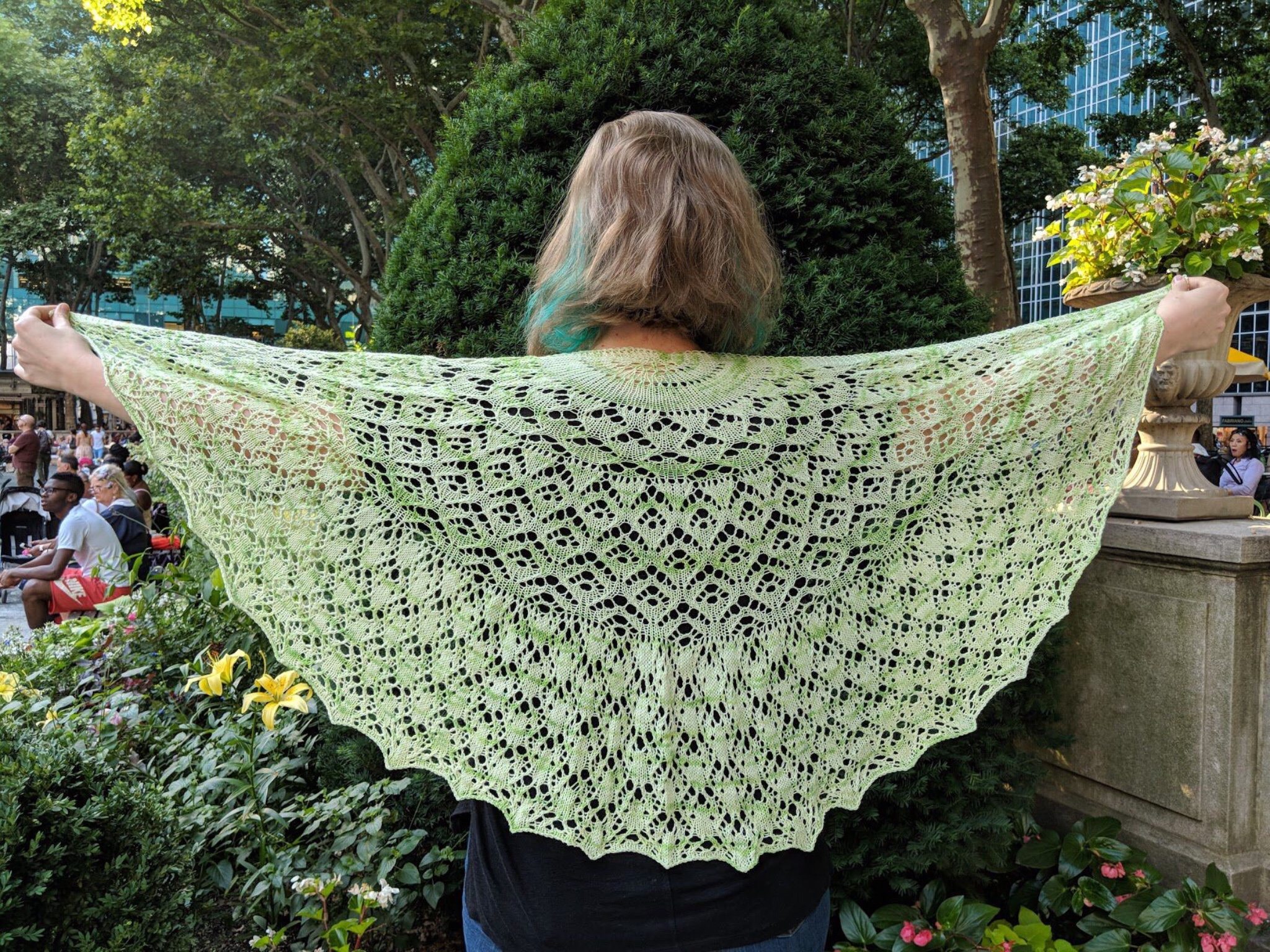 A green semicircular lace shawl being held up over the back of someone's shoulders