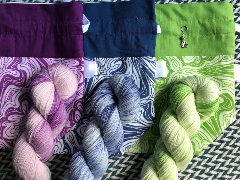 Three drawstring bags with three matching skeins of yarn