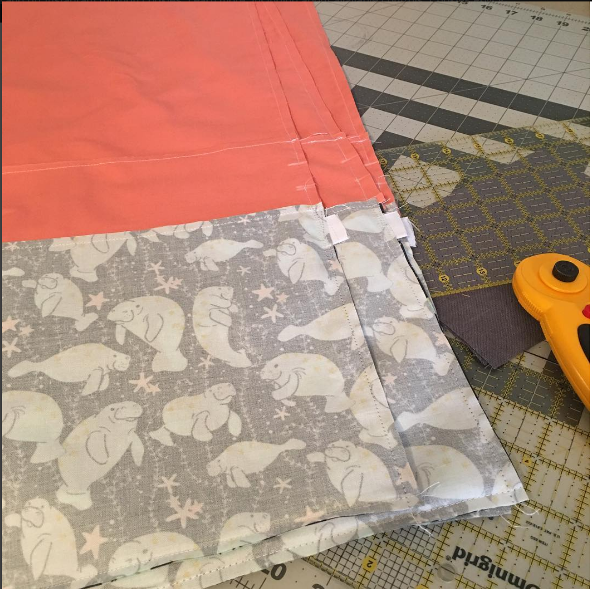 Stack of drawstring bags inside out half-sewn with coral fabric and rotary cutter