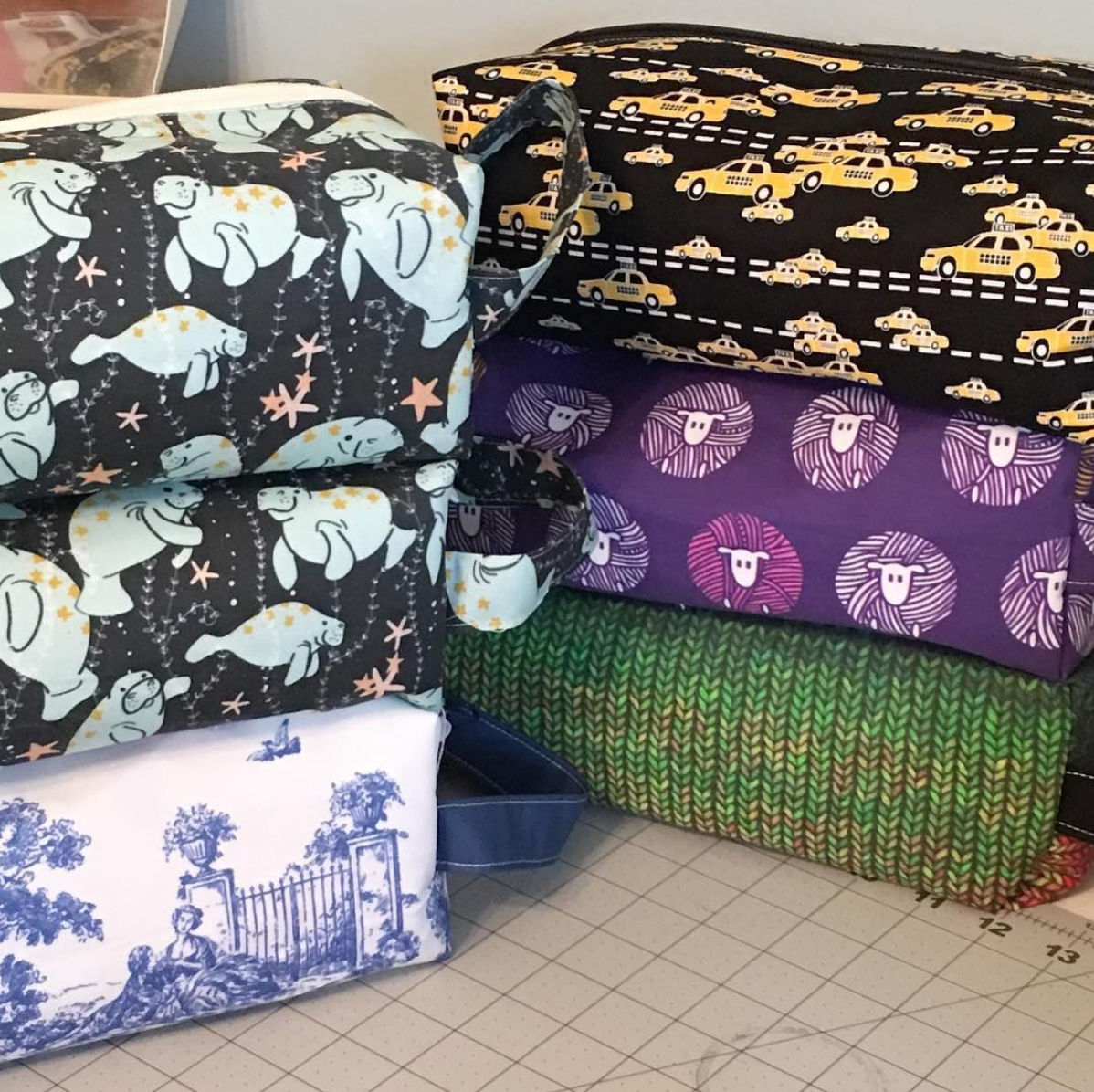 Photograph of stacked box bags in a variety of fabrics