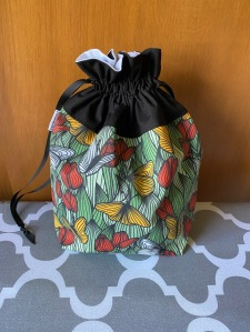 A drawstring bag with a black top and a green, yellow and red print of butterflies and tulips sits on an ironing board